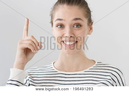 Closeup Shot Of Nice Smiling Young Caucasian Girl Isolated On Grey Background Pointing Finger Up To