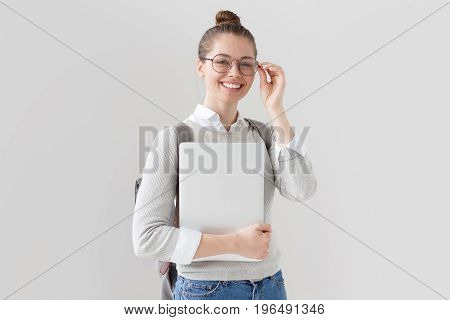 Indoor Shot Of University Student Girl Standing Isolated On Gray Background With Closed Laptop In Ha