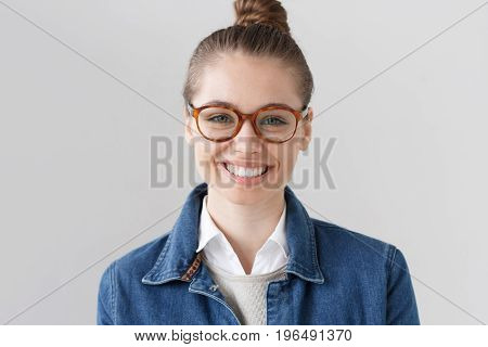 Indoor Portrait Of Beautiful University Student Girl Wearing Horn-rimmed Spectacles And Denim Jacket