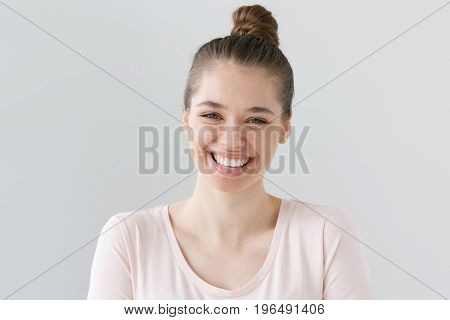 Closeup Of Positive Teenage Girl With Brown Hair Tied In Bun Isolated On Gray Background With Expres