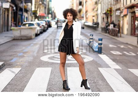 Young Black Woman With Afro Hairstyle Standing In Urban Background