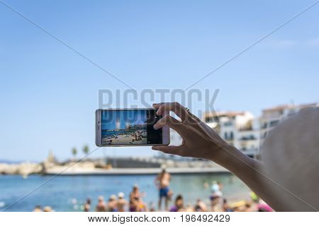 Hand held smartphone taking a picture in the urban beach of l'Escala. Costa Brava, Girona province, Spain.