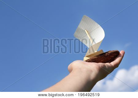 Small homemade sailing ship on the palm which is raised in the cloudless sky / My first startup