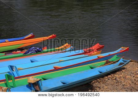 head of colorful long-tailed boats at riverside.