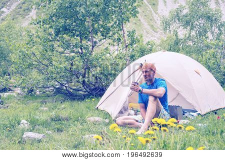 Bearded Man Traveler Is Resting Next To A Tent