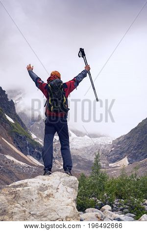 Happy Man Traveler With Open Arms Stands In The Mountain Gorge