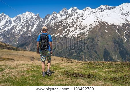 Man Hiker Goes Along Alpine Meadow To The Snow-capped Mountain Range
