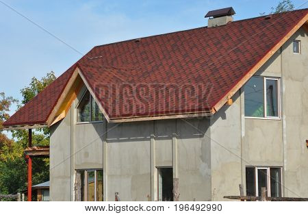 Attic construction mansard roof roof repair with asphalt shingles and plastering wall. Roofing construction.