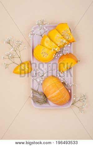 Slices Of Fresh Young Pumpkin On A Rectangular Pink Plate On An Orange Pastel Background..