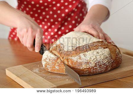 Woman Slicing Mixed Grain Bread. Selective focus.