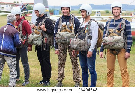 Sutiski, Ukraine - June 24, 2017: Skydivers carries a parachute after landing. Skydive Ukraine is the skydiving center located at Sutiski Aerodrome, about 20 km southwest of Vinitsa, Ukraine