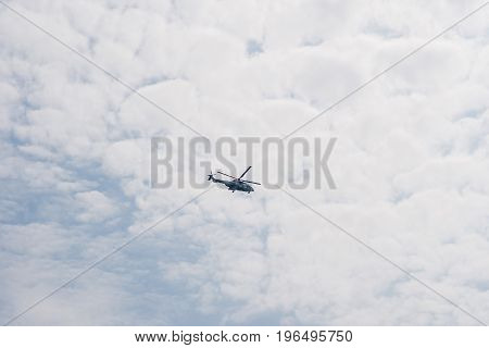 Helicopter Flying In The Sky Among The Clouds