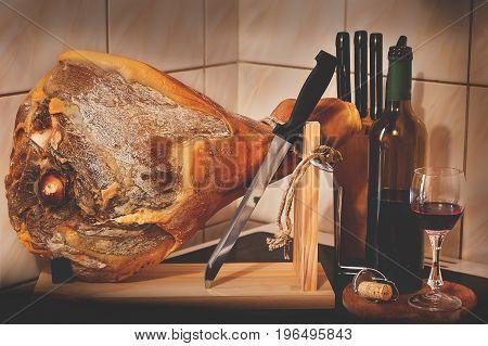 Spanish Jamon Serrano, tabla jamonera, jamonero knife with glass and bottle of wine. Food photo concept