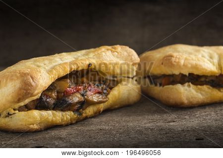 Puff pastry stuffed with mushrooms and vegetables on wooden background