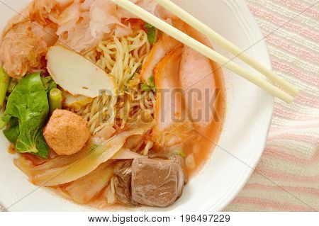 yellow noodles with squid and fish ball in red soup Chinese-language called Yong Tau Fu