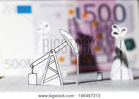 Petroleum pumpjack and oil rigs. Concept from paper against 500 euros on a blurry background. Shallow focus.