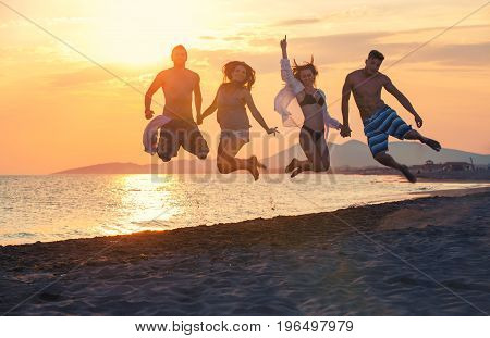 Group of happy people dancing and jumping inside sea on beautiful summer sunset
