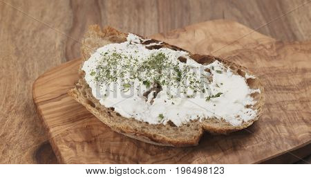 herbs fall on rustic bread with ricotta cheese, wide photo
