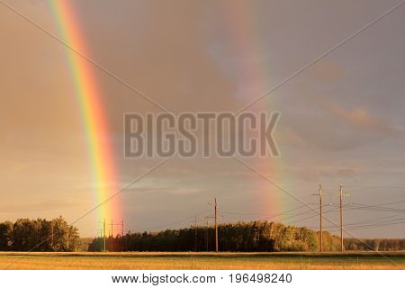 double rainbow after the rain against the backdrop of fields forests power lines / Expanded color palette of summer