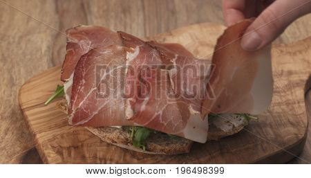 italian speck put on rustic bread with arugula and ricotta cheese, wide photo