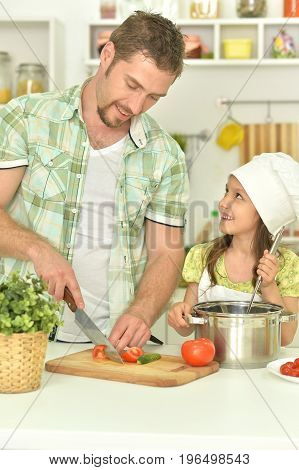 family together on the kitchen, man cutting vegetables