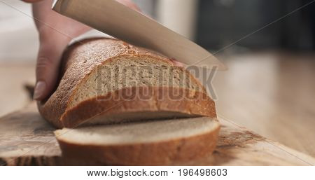 young female hands slicing rye wheat rustic bread on cutting board, wide photo