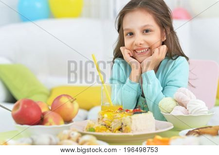 Cute little girl sitting at table with different sweets and fruits
