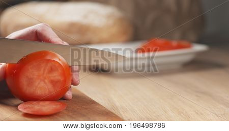 young man hands slicing tomato on cutting board, wide photo