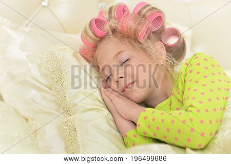 Portrait of cute little girl with pink hair curlers on head sleeping