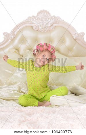 Portrait of cute little girl with pink hair curlers on head