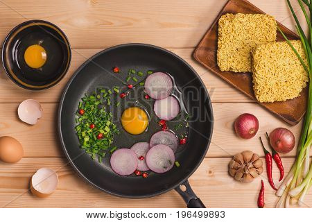 Instant Noodles For Cooking And Eat In The Dish With Eggs And Vegetables On Wooden Background.