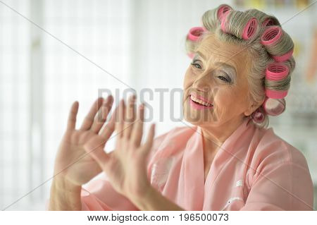 Close up portrait of senior woman in  bathrobe drying nail polish