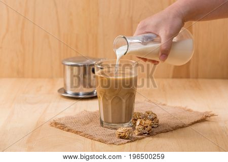 Pouring Milk In To Glass Of Coffee On A Wooden Table.