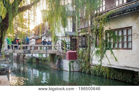 Suzhou, China - Nov 5, 2016: Ancient bridge and waterway at the historic Zhouzhuang Water Town. Image framed by an old willow tree.