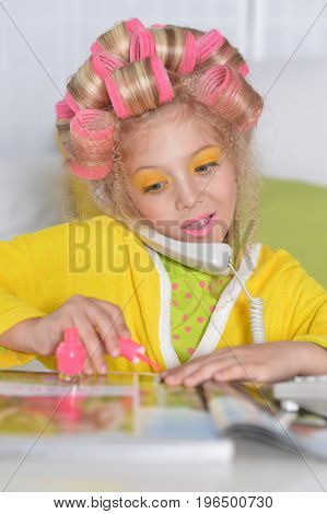 cute little girl polishing nails and talking on phone