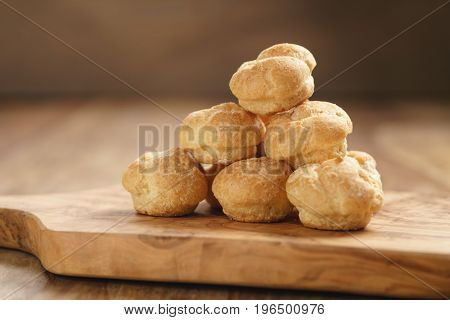 profiteroles on olive board closeup, shallow focus