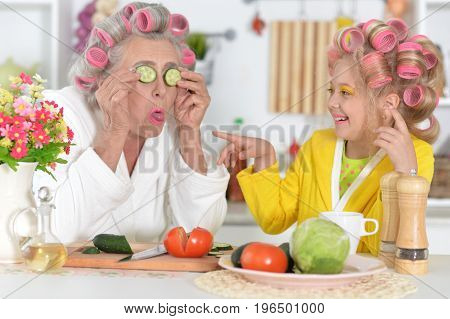 Senior woman and girl  with pink hair curlers on head sitting at table and using laptop making mask from cucumber slices