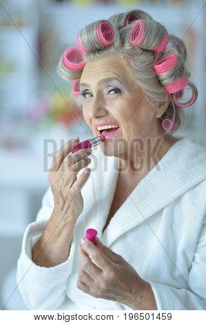 Close up portrait of senior woman in white bathrobe applying pink lipstick