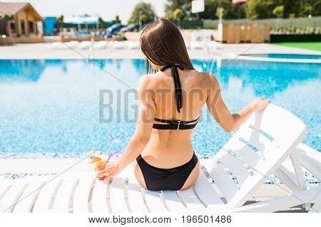 Woman Relaxing On Chaise Longue With Cocktail Rear View. Summer Time