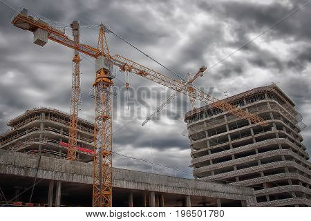 Industrial engineering. Construction crane on the construction site against the background of new real estate buildings. Concept of construction close-up.