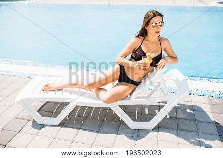 Young Woman In Swimsuit Relaxing With Cocktail Near Pool. Summer Time