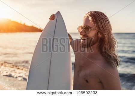 Young handsome man with long hair is standing on beach with white surfboard in hands and smiling.