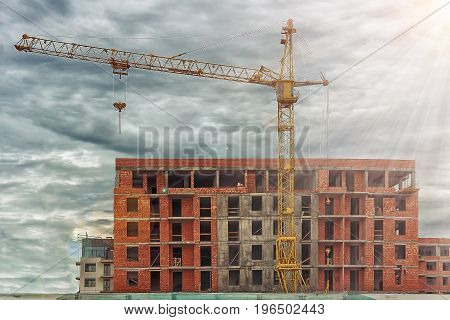 Construction crane on background of building shopping center building. Industrial construction of residential buildings and real estate. New house. concept of construction.