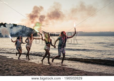 Group of young friends are having fun on beach with coloured smoke fires.