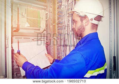 Electrician is repairing broken equipment. An electrician with circuit in his hands analyzes malfunction of electrical cabinet.