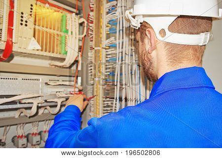 Engineer repairs electrical equipment. Electrical wires, terminals, equipment automation devices in one cabinet broke.