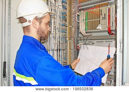 Engineer is looking at electrical drawing diagram in electrical automation cabinet and control of industrial equipment. professional electrician with circuit in his hands.