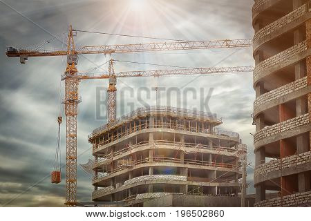 Industrial cranes build new concrete buildings on construction site. concept of construction. Construction of new square meters of real estate shopping centers and residential buildings.