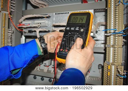 Electrician measures voltage of electrical circuit in control cabinet of industrial equipment. Electrical installation work by professional engineer.