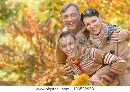 Portrait of happy young family in autumn park